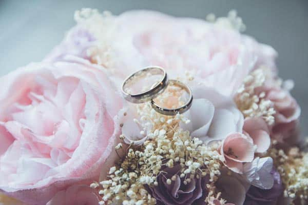 Gold-coloured Bridal Ring Set on Pink Rose Flower Bouquet
