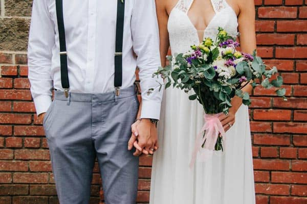 Wedding Bride and Groom Holding Hands Posing in Front of Photographer